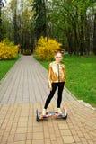 Una muchacha en una chaqueta del oro se coloca en la vespa de equilibrio del uno mismo en el parque imagen de archivo