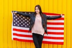 Una muchacha en una chaqueta negra con una bandera americana abierta Foto de archivo