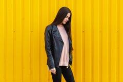 Una muchacha en una chaqueta negra mira abajo Fotos de archivo libres de regalías