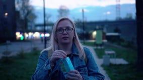 Una muchacha en una chaqueta y vidrios del dril de algodón está en la 'promenade' y el jugo de igualación de las bebidas de un tu almacen de metraje de vídeo