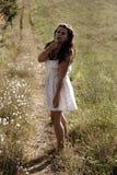 Una muchacha en el diente de león que sopla del vestido blanco Imágenes de archivo libres de regalías