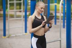 Una muchacha en el entrenamiento mira la tableta con una sonrisa Imagen de archivo