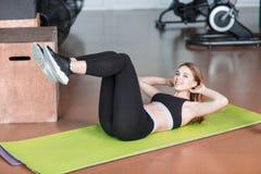 Una muchacha en el gimnasio pone en una estera verde de la aptitud balancea sus músculos abdominales Fotografía de archivo