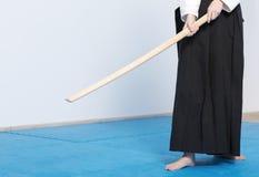 Una muchacha en el hakama negro que se coloca con la espada de madera Fotografía de archivo libre de regalías