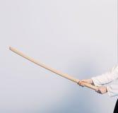 Una muchacha en el hakama negro que se coloca en actitud que lucha con la espada de madera Imagen de archivo
