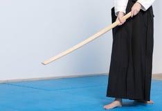 Una muchacha en el hakama negro que se coloca en actitud que lucha con la espada de madera Fotos de archivo