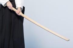 Una muchacha en el hakama negro que se coloca en actitud que lucha con la espada de madera Fotografía de archivo libre de regalías