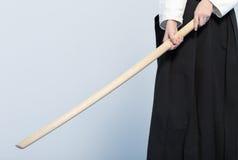 Una muchacha en el hakama negro que se coloca en actitud que lucha con la espada de madera bokken Fotografía de archivo