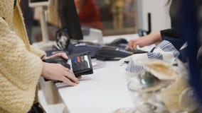 Una muchacha en el pago y envío en una tienda de ropa del ` s de las mujeres Fotografía de archivo