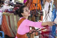 Una muchacha en el traje nacional que trabaja en mano-tejer tradicional imagenes de archivo
