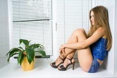 Una muchacha en el Windowsill Imágenes de archivo libres de regalías