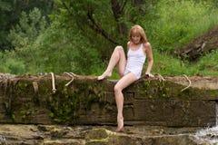 Una muchacha en la alineada blanca en una presa vieja. Foto de archivo libre de regalías