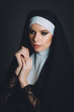 Una muchacha en la imagen de una monja imagenes de archivo