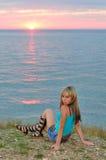 Una muchacha en la puesta del sol en la playa Fotos de archivo libres de regalías