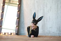 Una muchacha en una máscara negra imagenes de archivo