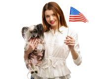 Una muchacha en una mano sostiene una bandera americana y en su segunda mano sostiene un perro con cresta chino Aislado imagenes de archivo