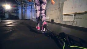 Una muchacha en medias grises entra en el gimnasio y saca la cazadora almacen de metraje de vídeo