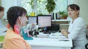 Una muchacha en una recepción del ` s del doctor Un doctor de sexo femenino lleva a cabo una conversación con un paciente almacen de metraje de vídeo