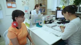Una muchacha en una recepción del ` s del doctor Un doctor de sexo femenino lleva a cabo una conversación con un paciente metrajes