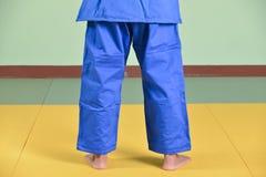 Una muchacha en soldado enrollado en el ejército azul del judo imagen de archivo