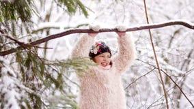 Una muchacha en un abrigo de pieles rosado se está divirtiendo con un parque del invierno Resto activo, ocio del ` s de los niños almacen de video