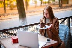 Una muchacha en un café al aire libre con un ordenador portátil que habla con alguien vía una llamada video, mostrando su torta imagen de archivo