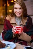 Una muchacha en un café está sosteniendo una taza con una bebida Fotografía de archivo libre de regalías