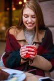 Una muchacha en un café está sosteniendo una taza con una bebida Imagenes de archivo
