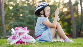 Una muchacha en un casco protector está jugando en una tableta, al lado de ella es pcteres de ruedas almacen de metraje de vídeo