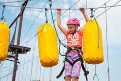 Una muchacha en un casco rosado supera obstáculos en el teleférico en un parque extremo fotografía de archivo