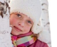 Una muchacha en un casquillo blanco en el abedul en invierno Imagen de archivo