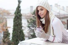 Una muchacha en un CASQUILLO se coloca en la calle con una taza de café Fotos de archivo libres de regalías