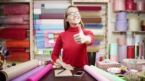 Una muchacha en un delantal rayado y una camisa de tela escocesa se coloca en una floristería y dobla sus manos en su pecho que s almacen de metraje de vídeo