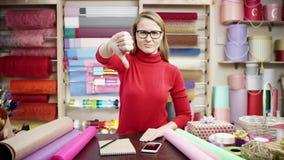 Una muchacha en un delantal rayado y una camisa de tela escocesa se coloca en una floristería y dobla sus manos en su pecho que s almacen de video
