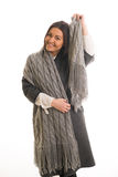 Una muchacha en un gris hizo punto la sonrisa de la bufanda Fotografía de archivo libre de regalías