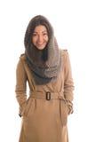 Una muchacha en un gris hizo punto la sonrisa de la bufanda Imagen de archivo libre de regalías