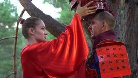 Una muchacha en un kimono rojo saca un casco de un samurai en armadura roja en el medio de un bosque conífero almacen de video