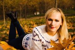 Una muchacha en un parque del otoño Fotos de archivo