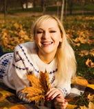 Una muchacha en un parque del otoño Imagenes de archivo