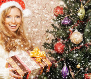 Una muchacha en un sombrero de la Navidad que presenta cerca del árbol Fotografía de archivo