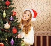 Una muchacha en un sombrero de la Navidad que presenta cerca del árbol Foto de archivo libre de regalías