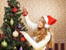 Una muchacha en un sombrero de la Navidad que presenta cerca del árbol Fotos de archivo