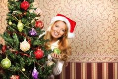 Una muchacha en un sombrero de la Navidad que presenta cerca del árbol Imagenes de archivo