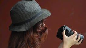 Una muchacha en un sombrero hace las fotos con una cámara de DSLR Primer almacen de video