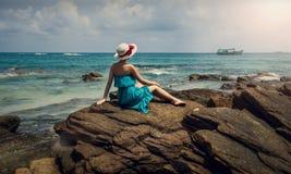 Una muchacha en un sombrero se sienta en una roca Una muchacha en las rocas por el mar Foto de archivo