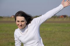 Una muchacha en un suéter blanco que agita su mano y alegre imagen de archivo libre de regalías