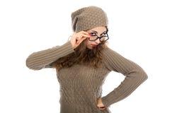 Una muchacha en un suéter gris y los vidrios que miran la cámara Imagenes de archivo
