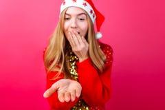 Una muchacha en un suéter rojo, sombrero de Papá Noel, llevando a cabo algo invisible en sus palmas, y mirándolo con la admiració imagen de archivo libre de regalías