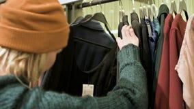 Una muchacha en un suéter verde y un sombrero amarillo camina a través de una tienda de cosas y elige qué comprar Cosas de los ta metrajes