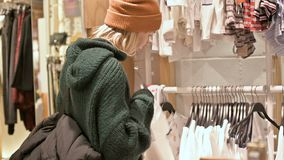 Una muchacha en un suéter verde y un sombrero amarillo camina a través de una tienda de cosas y elige qué comprar Cosas de los ta almacen de video